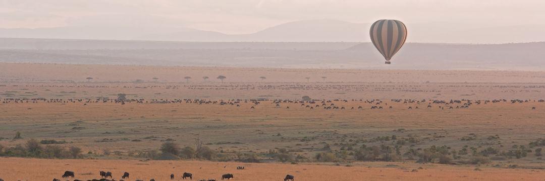 Hot air balloon floating across the Masai Mara