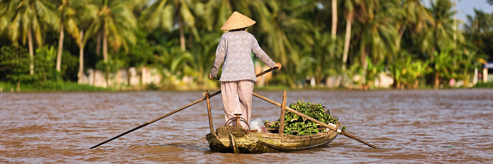 Vietnamese woman rowing a boat in the Mekong River Delta