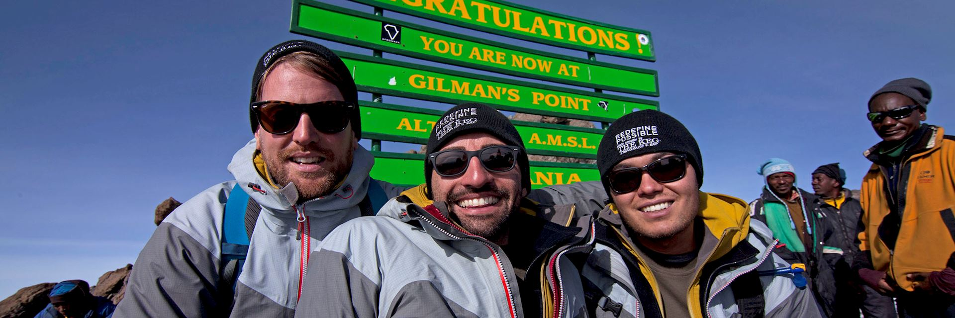 Spencer West (middle) celebrates reaching the top of Mount Kilimanjaro