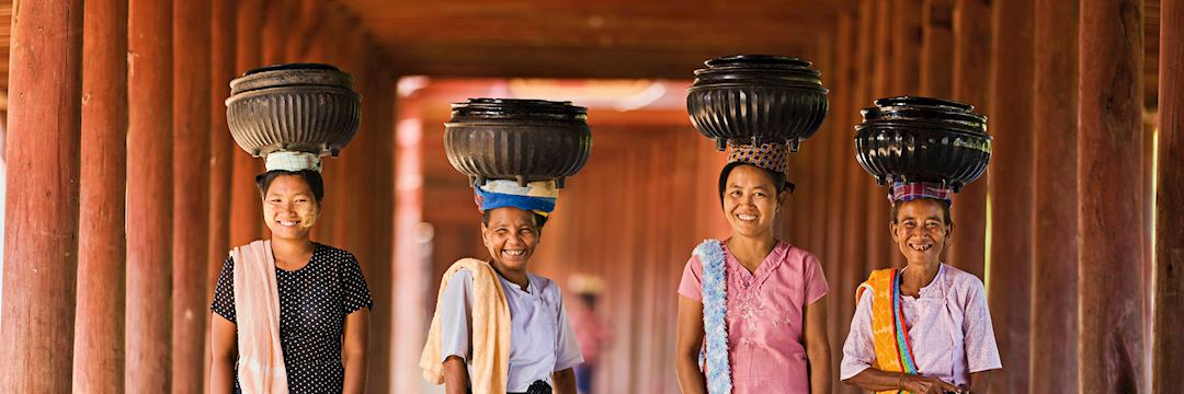 Local women carrying bowls of rice to a monastery, Burma (Myanmar)