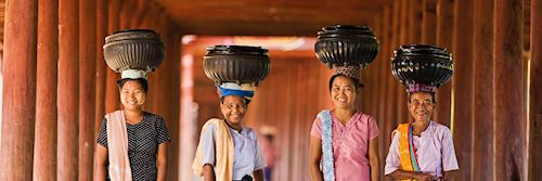 Local women carrying bowls of rice to a monastery, Myanmar