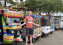 Tom next to chiva ((Spanish for goat)) buses in Guatepe, Medellin, Colombia