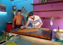 Mat helping a local make pancakes in Ayuthaya, Thailand